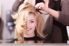 Smiling girl with blond wavy hair by hairdresser in beauty salon. Beautiful smiling girl with blond wavy hair by hairdresser. Hairstylist with comb combing