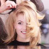 Smiling girl with blond wavy hair by hairdresser in beauty salon Stock Photo