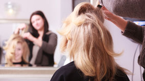 Smiling girl with blond wavy hair by hairdresser in beauty salon. Beautiful smiling girl with blond wavy hair by hairdresser. Hairstylist combing female client Royalty Free Stock Photo