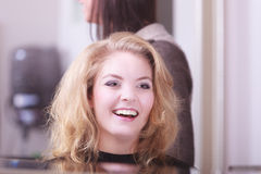 Smiling girl with blond wavy hair by hairdresser in beauty salon Stock Image