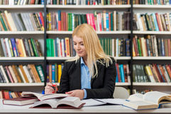 Smiling girl with blonde hair sitting at a desk in the lib Royalty Free Stock Images