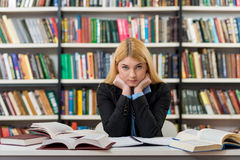 Smiling girl with blonde hair sitting at a desk in the lib. Smiling young girl with blonde hair sitting at a desk in the lib Stock Photography