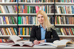 Smiling girl with blonde hair sitting at a desk in the lib. Smiling young girl with blonde hair sitting at a desk in the lib royalty free stock photo