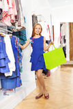 Smiling girl in blue dress with shopping bag. Smiling beautiful girl in blue dress with bright shopping bag standing in the clothing store Royalty Free Stock Images