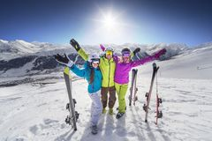 Smiling girl in blue jacket skiing alps resort. Female and male young people having skiing and snowboarding vacation on a snow slopes Stock Image