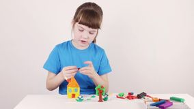 Smiling girl in blue molds house from plasticine on white table stock video footage