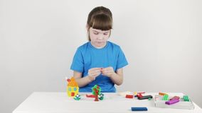 Smiling girl in blue molds house from plasticine on white table. In white room stock video