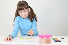 Smiling girl in blue watercolor paints butterfly on table. In white room royalty free stock photo