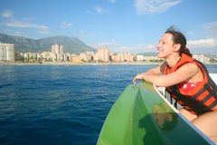 A smiling girl in a boat in the lifejacket. Admiring views of the coastline, focus on the girl Stock Images