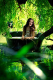 A smiling girl in a boat. Under the willow Royalty Free Stock Photos