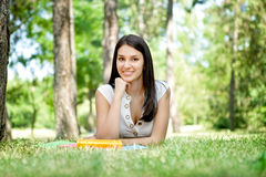 Smiling girl with book in park Royalty Free Stock Photography