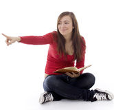 Smiling girl with book, pointing Royalty Free Stock Image