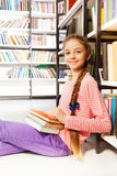 Smiling girl with books sit on floor in library Stock Photos