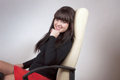 Smiling girl in boss chair Stock Images