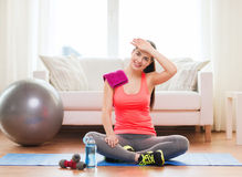 Smiling girl with bottle of water after exercising. Fitness, home and diet concept - smiling teenage girl with bottle of water after exercising at home Stock Image