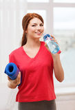 Smiling girl with bottle of water after exercising Stock Photography