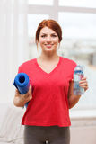 Smiling girl with bottle of water after exercising Royalty Free Stock Photo