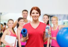 Smiling girl with bottle of water after exercising. Fitness, home and diet concept - smiling teenage girl with bottle of water and yoga mat after exercising at Stock Photo