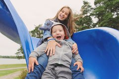 Smiling girl and boy having fun on children`s slide. Outdoor portrait of a cute children at playground Stock Photos