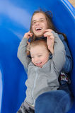 Smiling girl and boy having fun on children`s slide. Outdoor portrait of a cute children at playground Stock Image