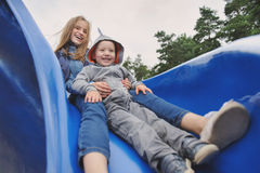 Smiling girl and boy having fun on children`s slide. Outdoor portrait of a cute children at playground Royalty Free Stock Images