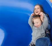 Smiling girl and boy having fun on children`s slide. Outdoor portrait of a cute children at playground Stock Photo