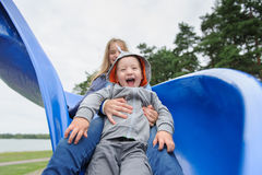 Smiling girl and boy having fun on children`s slide. Outdoor portrait of a cute children at playground Royalty Free Stock Photography
