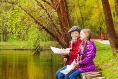 Smiling girl and boy sit near nice pond playing Stock Photo