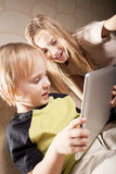 Smiling girl and boy with tablet computer Stock Photos
