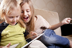 Smiling girl and boy with tablet computer Stock Image