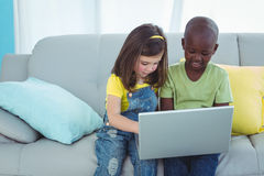 Smiling girl and boy using a laptop Stock Photo