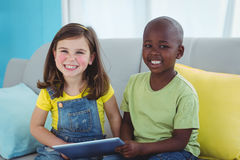 Smiling girl and boy using tablet Stock Image