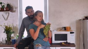 Smiling girl with boyfriend in flat. Portrait attractive young couple at home. Caucasian blonde woman and handsome man with beard and mustache eating grapes in stock footage