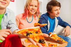 Smiling girl and boys holding pizza pieces at home Royalty Free Stock Images