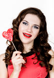 Smiling girl with braces holding heart candy posing on a white background