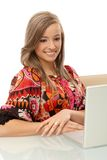 Smiling girl browsing internet on laptop Stock Photo