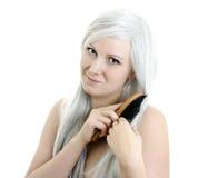 Smiling girl brushing hair Stock Image