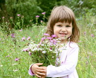 Smiling Girl with Bunch of Flowers. Little Smiling Girl with Bunch of Flowers Portrait Royalty Free Stock Photography