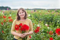 Smiling girl with bunch of red dahlias Royalty Free Stock Photos