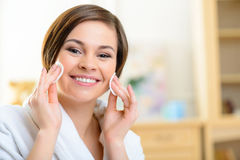 Smiling girl is busy removing make up stock images