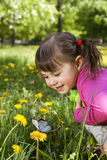 A smiling girl with a butterfly. A smiling girl wearing a pink shirt, sitting on the dandelion field and observing a butterfly Stock Photos