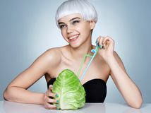 Smiling girl with cabbage cocktail. Photo of fashion blonde girl on blue background. Detox concept Royalty Free Stock Photos