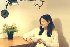 Smiling girl in a cafe drinking coffee stock image