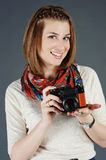 Smiling girl with a camera Stock Images