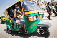 The smiling girl with camera on a tuk-tuk. Stock Images