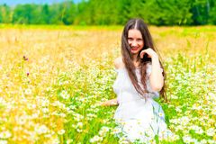 Smiling girl in camomile field rests Stock Photo