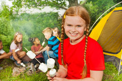 Smiling girl camping and holding  marshmallows Stock Photography