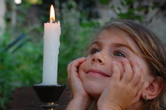 Smiling Girl and candle. Little girl looking at the fire of the candle Royalty Free Stock Photography
