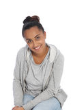 Smiling Girl in Casual Clothing Sitting on Floor. Close up Smiling Young Woman Wearing Casual Clothing Sitting on the Floor While Looking at the Camera. Isolated Stock Images