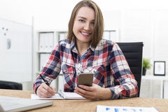 Smiling girl with cell phone writing Royalty Free Stock Images